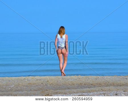 poster of Girl On The Beach By The Sea, The Sky With The Sea Merged Into One Space. The Sea Has An Exceptional