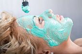 pic of mud pack  - Applying mud face pack on woman face with brush - JPG
