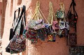 stock photo of zoroastrianism  - Embroidered oriental patterned purses stacked on bazaar in Abyaneh - JPG
