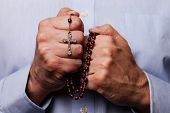 Male hands praying holding a beads rosary with Jesus Christ in the cross or Crucifix on black backgr poster