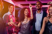 Cheerful girl dancing at night party with her friends. Beautiful young woman and smiling men having  poster