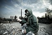 image of breather  - Scientist with gas mask examining rock in destroyed territory after explosion - JPG