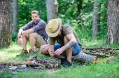 Camping In Forest. Men On Vacation. Man Brutal Bearded Hipster Prepares Bonfire In Forest. Ultimate  poster