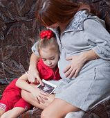 a pregnant woman with her daughter looks at picture with ultrasound on the sofa