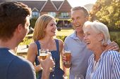 Parents With Adult Offspring Enjoying Outdoor Summer Drink At Pub poster