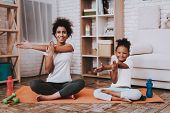 Mulatto Mother And Young Daughter Train Together. People And Dumbbells. Yoga With Little Daughter An poster