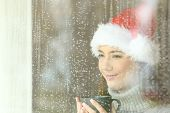 Happy Woman Looking Through A Window In Christmas Time In A Rainy Day poster