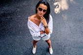 Contrast Portrait Of A Brunette In Sunglasses. A Middle-aged Woman In A Shirt And Shorts. poster