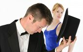 Focus on woman.  Beautiful young woman in blue formal looking at camera behind attractive young man in tux. poster