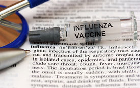 picture of avian flu  - A syringe containing the influenza vaccine laid on a doctors medical dictionary open at the influenza page - JPG