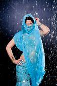 picture of dancing rain  - girl executes east dance in the rain against a dark background - JPG
