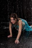 stock photo of dancing rain  - girl executes east dance in the rain against a dark background - JPG