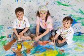 stock photo of children playing  - Children playing with painting with the background painted - JPG
