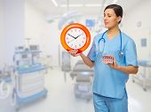 Doctor with pills and clock at medical office