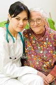 stock photo of health-care  - A young female doctor sitting next to an old woman - JPG