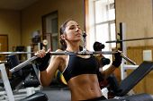 picture of lats  - Sports young woman doing exercises in the gym on Lat Machine - JPG