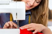 Freelancer - Fashion designer or Tailor working on a design or draft, she sews with a sewing machine
