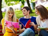 Group happy student with notebook on bench outdoor.
