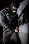 stock photo of scumbag  - Robber and the car thief in a mask opens the door of the car and hijacks the car - JPG