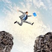 pic of gap  - Image of young businessman jumping over gap - JPG