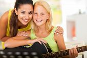stock photo of tutor  - attractive music tutor and preteen girl with a guitar - JPG