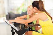 stock photo of  preteen girls  - young preteen girl having guitar lesson at home - JPG
