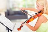 stock photo of preteen  - cheerful talented preteen girl playing violin at home - JPG