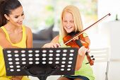 stock photo of violin  - cheerful pre teen girl enjoying her violin lesson with music teacher at home - JPG