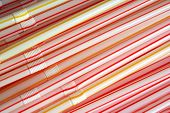stock photo of non-biodegradable  - plastic drinking straws with red and yellow stripes - JPG