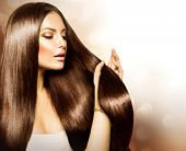 Hair. Beauty Fashion Model Woman touching her Long and Healthy Brown Hair. Beauty Brunette Girl isol