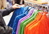 Close-up hands of man choosing t-shirt and parka during clothing shopping at store