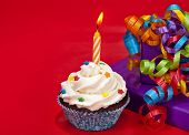 stock photo of sprinkling  - A birthday cupcake with colorful sprinkles on a red background with presents and ribbon - JPG