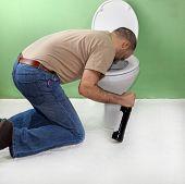 pic of puke  - Drunk man with wine bottle vomiting in toilet - JPG