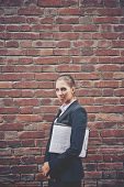 Image of angry businesswoman with document walking along brick wall