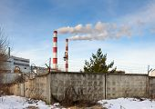 stock photo of chp  - smokestack pipe electric generating company behind the fence - JPG
