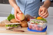 stock photo of lunch box  - A woman preparing a lunch packet for work - JPG