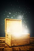 image of wooden crate  - Open magical Wooden crate box on the floor with shiny particles flying arround - JPG