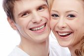 Faces of amorous young couple looking at camera with toothy smiles