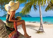Beautiful woman with straw hat and sarong on the beach. Thailand.
