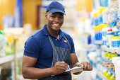 pic of supermarket  - happy african shop assistant checking stock in supermarket - JPG