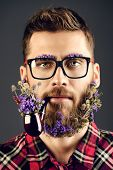 pic of peace-pipe  - Handsome young man in glasses and a beard of flowers smoking a pipe - JPG