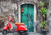 stock photo of vespa  - Photo of red scooter near green door and palm - JPG