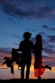 image of western saddle  - A silhouette of a cowboy holding on to his saddle and his girl at the same time - JPG