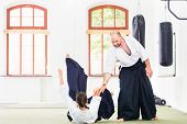 picture of aikido  - Man and woman fighting at Aikido training in martial arts school  - JPG