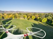 stock photo of morning  - drone flying over a park in fall colors under morning light with deep long shadows - JPG