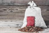 pic of thrift store  - Concept of the thrift storing - Red rice in the burlap sack with the patch on a wooden background