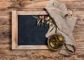 picture of slating  - Overhead view of a olive oil with olive twig and linen napkin on an old school slate over a rustic wooden background - JPG