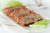 stock photo of meatloaf  - a serving platter of sliced turkey meatloaf with spinach and sundried tomatoes - JPG