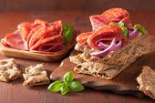 stock photo of crisps  - Crisp bread with salami and red onion - JPG
