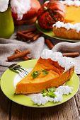 image of pumpkin pie  - Piece of homemade pumpkin pie on plate on wooden background - JPG